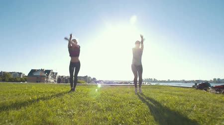 backflip : Two caucasian young women jumping in twine on the grass at sunny day