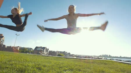 sznurek : Two young women performing acrobatic jumps on the grass under the sun Wideo