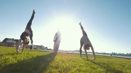 backflip : Young women performing acrobatic wheel on the grass, silhouette of young man standing in center of them
