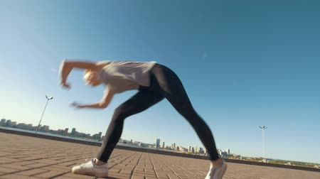 backflip : Young caucasian woman performs acrobatic flip on the asphalt on background cityscape
