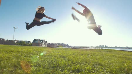 backflip : Young sporty women performing synchronous acrobatic elements on the grass under the sun