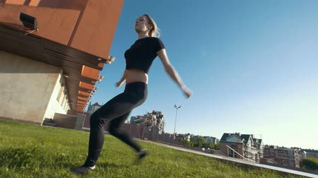 backflip : Slim young woman performs acrobatic jump on the grass on background cityscape