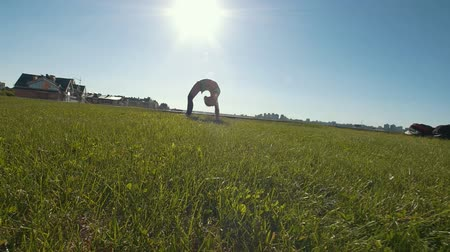 backflip : Young female gymnast performs gymnastic bridge on the grass in sunny day