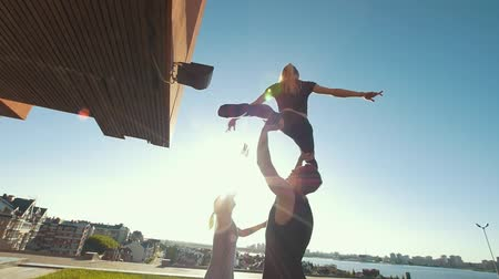 backflip : Team of cheerleaders practice outdoors at summer day - muscular man young woman support the girl in air