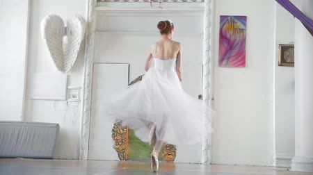 bale : Young beautiful ballerina in white dress performs dance in spacious white studio