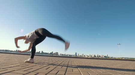 sznurek : Young caucasian woman performs acrobatic flip on the asphalt on background cityscape