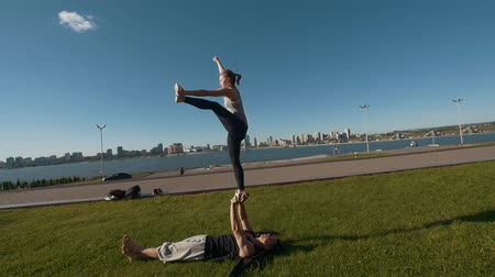 backflip : Young sporty couple practicing acrobatics performing front plank bird pose, young man holding flying woman balancing on his arms outdoors at sunset Stock Footage