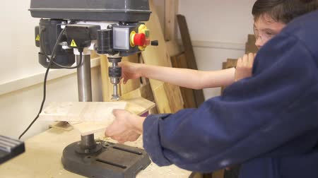 chisel : Father and son drills the wooden plank using joinery machine in carpentry workshop Stock Footage