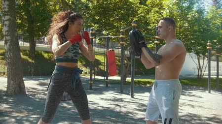 gumka : Young man teaches beautiful woman boxing blows outdoors at sunny day, slow-motion