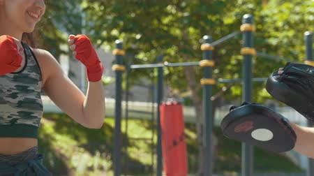 striptiz : Young muscular man and woman engaged in boxing in the park ar sunny day Stok Video