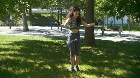 bandagem : Young slender woman jumping with a rope, boxing workout outdoors at sunny day