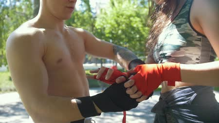 gumka : Male boxer wrap his hands young woman helps him, workout in the park - slowmotion Wideo