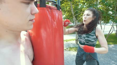 bandage : Young man holds punching bag to athletic woman engaged in boxing in the park at sunny day, slow-motion Stock Footage