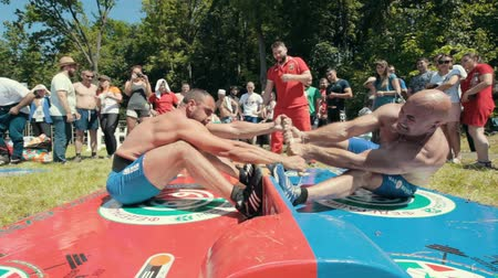 zapasy : KAZAN, RUSSIA - JUNE 23, 2018: Traditional Tatar festival Sabantuy - Strong men wrestling outdoors at summer day
