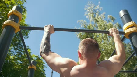 bandagem : Rear view of muscular man pulled-up on horizontal bar outdoors at sunny day