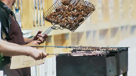 кусок : Hands of men grilling kebab on barbecue outdoors