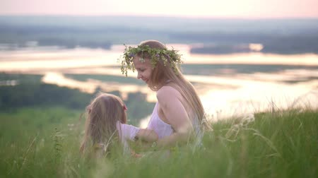Happy mother and daughter having a rest in nature on the hill at summer sunset