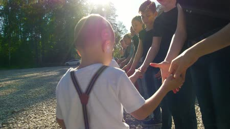 skarpetki : Teenagers and children teams greeting each other with shake hands at summer sunny day