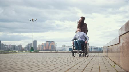 chlapík : Disabled man in a wheelchair with young woman walking at the city street