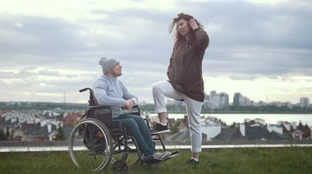 chlapík : Happy disabled man in a wheelchair embraces with young woman outdoors