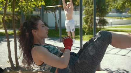 bandage : Sportive woman doing fitness exercises in front of muscular man athlete pulled-up on the bar outdoors at sunny day, slow-motion