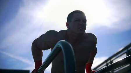 paralelo : Young muscular sportsman pushing up at the parallel bars - workout at summer outdoor, slow-motion Vídeos
