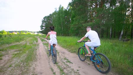 önlem : Young couple cycling through the spruce branches in summer forest Stok Video