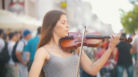 senfoni : Young female violinist playing a fiddle on pedestrian street at summer day
