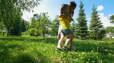 from behind : Happy little boy and girl siblings having fun and hugging outdoors at summer day