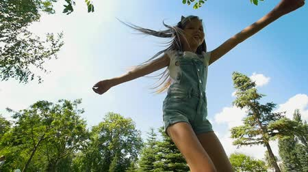 детская площадка : Happy little girl with long hair having fun in summer park