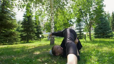 legginsy : Little girl performs somersaults on green grass in the park at summer Wideo