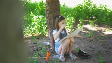 гуашь : Little caucasian girl drawing with brush sitting under the tree at summer