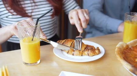 twaróg : Young woman cuts a tasty croissant with a knife and fork eating in restaurant Wideo