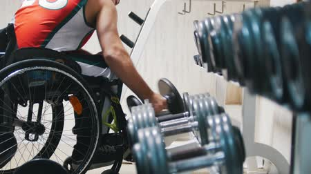 resistência : Disabled in a wheelchair pulls up and takes the weight in the gym while training.