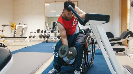 příklad : Handsome disabled man in a wheelchair trains in a gym with weights.