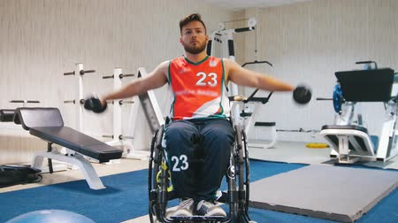 příklad : Handsome disabled man in a wheelchair raises his arms with dumbbells in the gym during training.