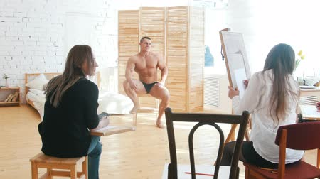 exercício : Girls draws a muscular shirtless guy on a canvas, theyre having fun