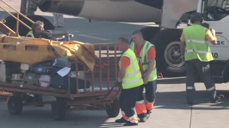 carregamento : 15 august 2018, Moscow, Russia - Airport staff in reflective vests move the trolley with luggage load