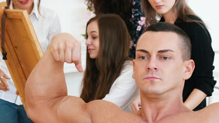 exercício : Girls sitting behind an easel draws a muscular shirtless guy on a canvas.