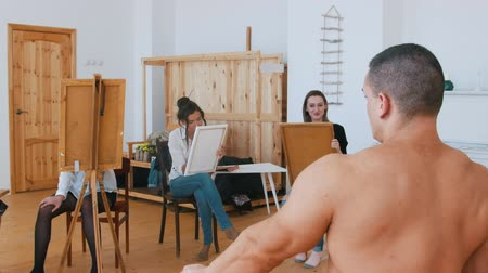 exercício : Girls draws a muscular shirtless guy on a canvas