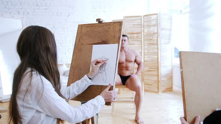 exercício : Girl draws a muscular shirtless guy on a canvas. Guy in focus Vídeos