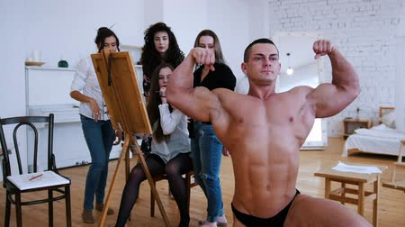 exercício : Handsome shirtless muscular guy is posing for girls artists