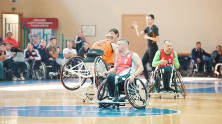 impaired : Kazan, Russia - 21 september 2018 - Disabled person rises from the floor to the wheelchair while playing wheelchair basketball Stock Footage