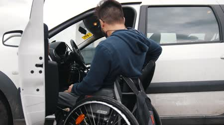 cripple : Disabled man at wheelchair gets in car Stock Footage