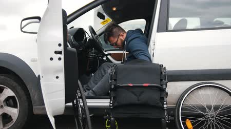 cripple : Disabled man in a car put together his wheelchair and picks it up in a car