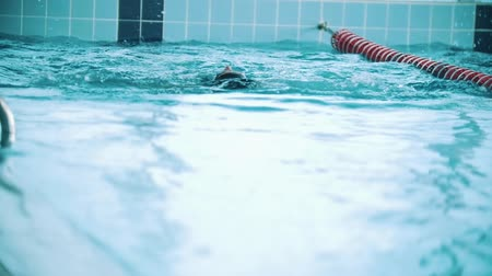 submarino : Disabled man swims on the back in a swimming pool. Slow motion Stock Footage