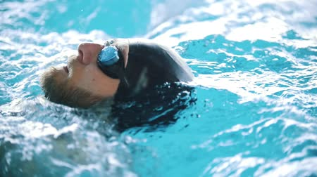 motyl : Disabled man swims on the back in a swimming pool. Close up shot. Slow motion