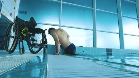 plavec : Disabled man gets out of the swimming pool. Side view