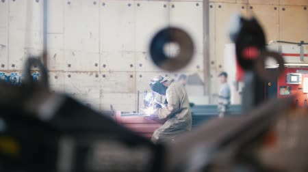 welding helmet : Welder at an industrial factory works in a special suit and mask Stock Footage
