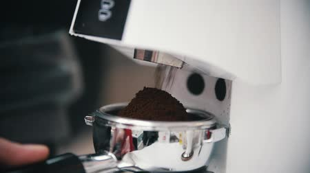 официант : Barista filled up a holder with a ground coffee. Close up